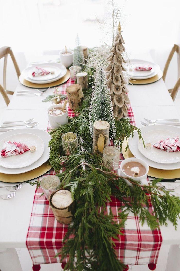 table de noel rouge et blanc avec des branches de sapin et des bougies decoration cosy et rustique