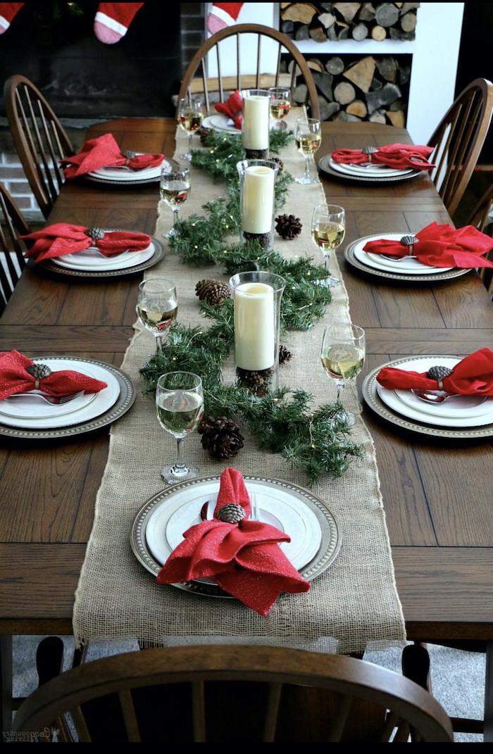 table de noel rouge et blanc avec des element naturels un guirlande verte et cones depin