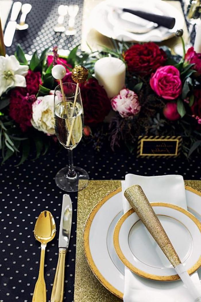 table de nouvel an avec des decoration de fleurs et une thematique en noir et or déco de table pour nouvel an