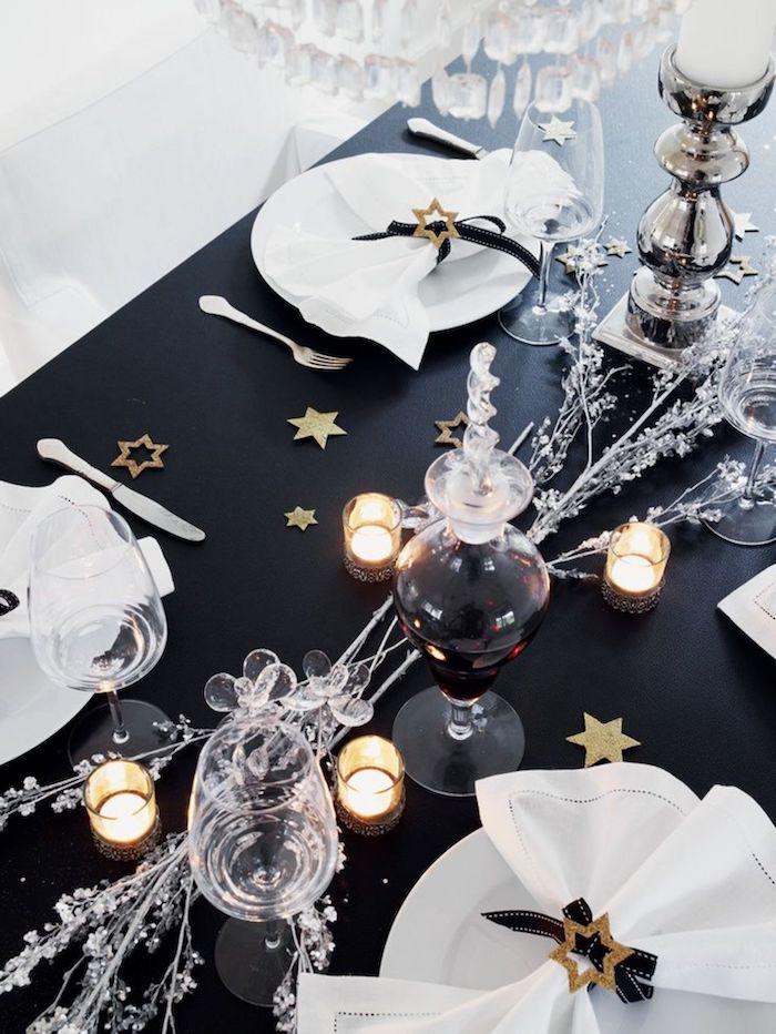 table de nouvel an en thematique noir avec des elements scintillantes comme des branches argentines et des etoiles decoratives dores