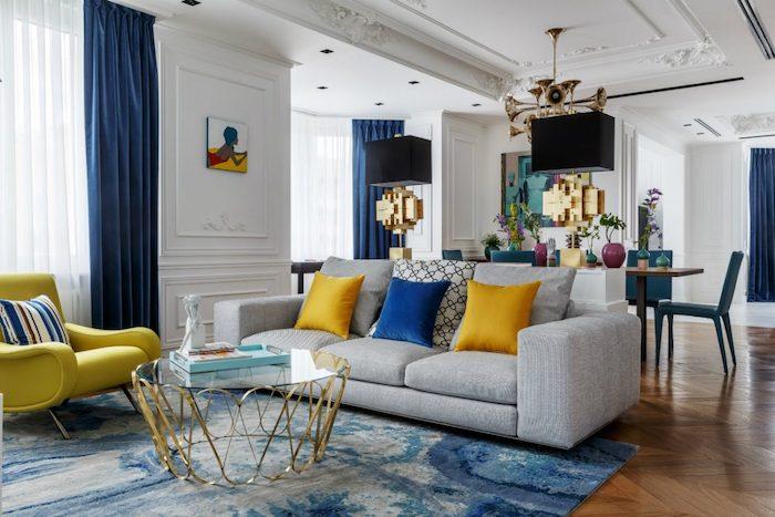 tendance deco 2021 avec un canape gris et des coussins en jaune lumineux et bleu francais