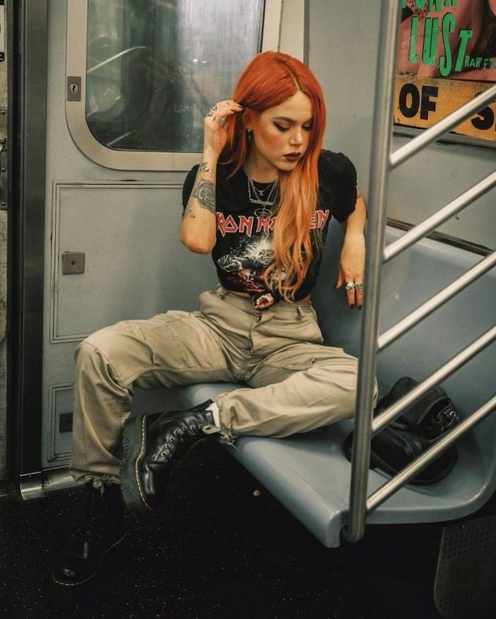 tenue aesthetic années 90s avec des bottes en cuir et t shirt iron maiden avec des cheveux tintes en rouge