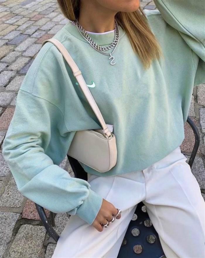 tenue aesthetic fille ado vetue en pantalon blanc une blouse sportif et un petit sac a main