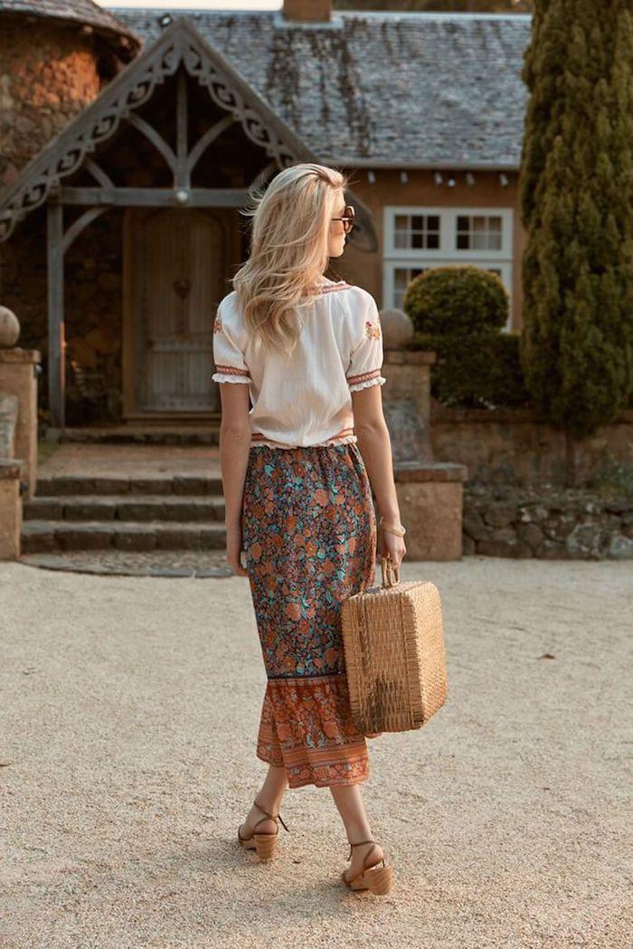 tenue aesthetic style boho chic une femme blonde devant une maison rustique vetue en jupe maxi florale portante une valise