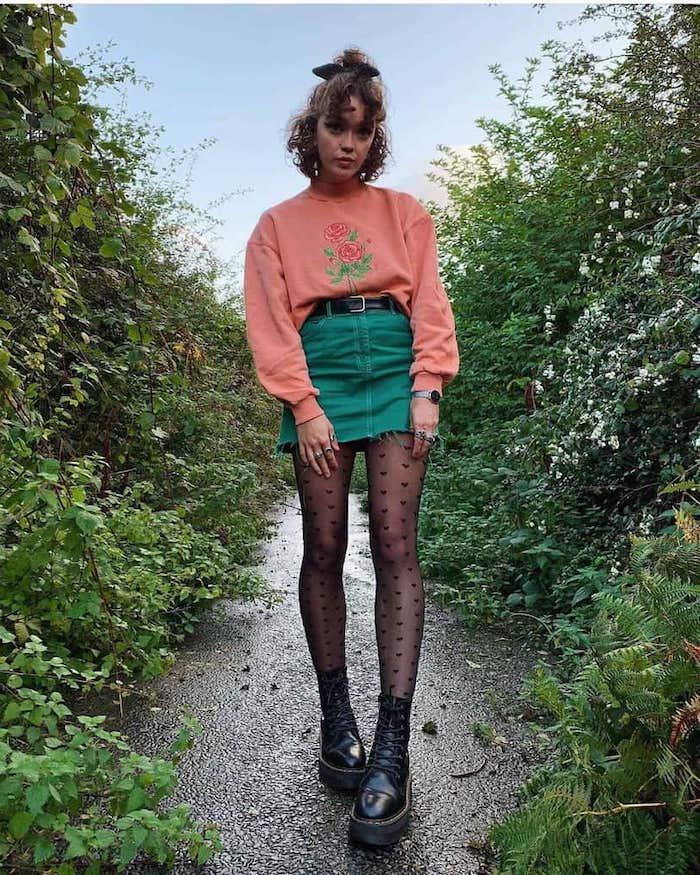 tenue stylée femme des années 90s soft grunge aec une jupe courte en jean vert pull rose et bottes noires avec un collant a pois dans la nature