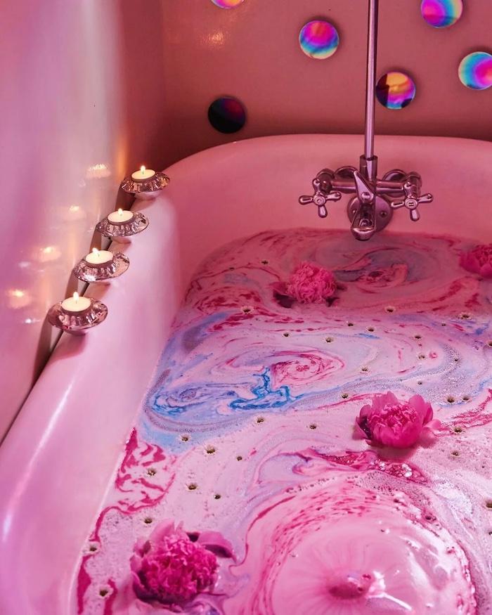 un bain plein d eau avec des boules de bain disperse et des fleurs quatres bougies a cote