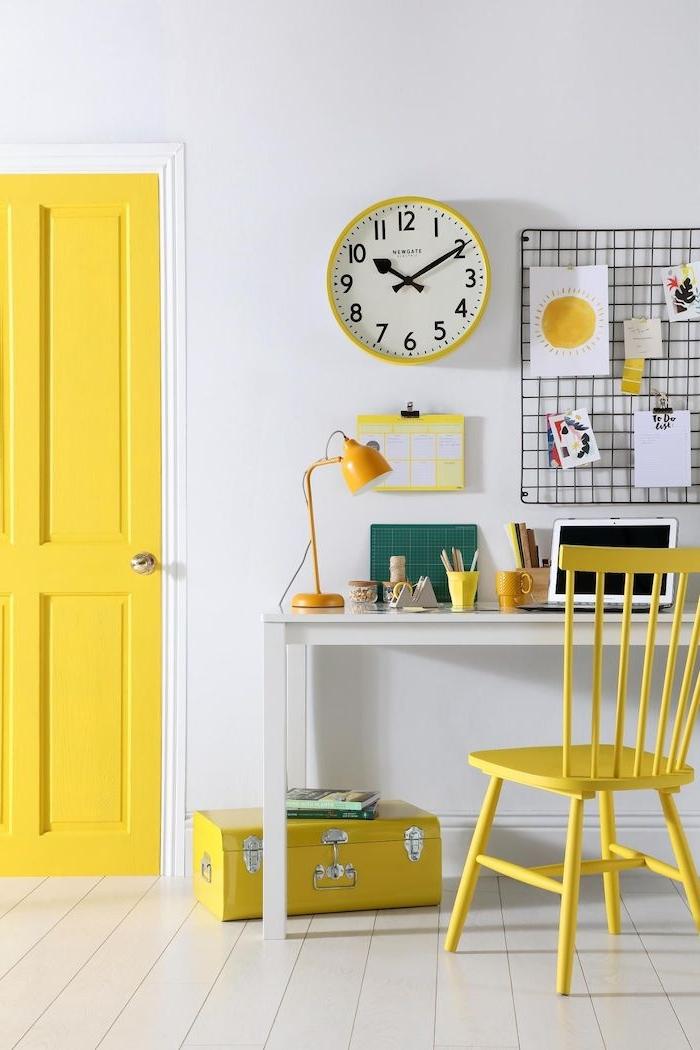 un bureau avec des elements en jaun un horloge au mur et valise au sol couleur tendance 2021