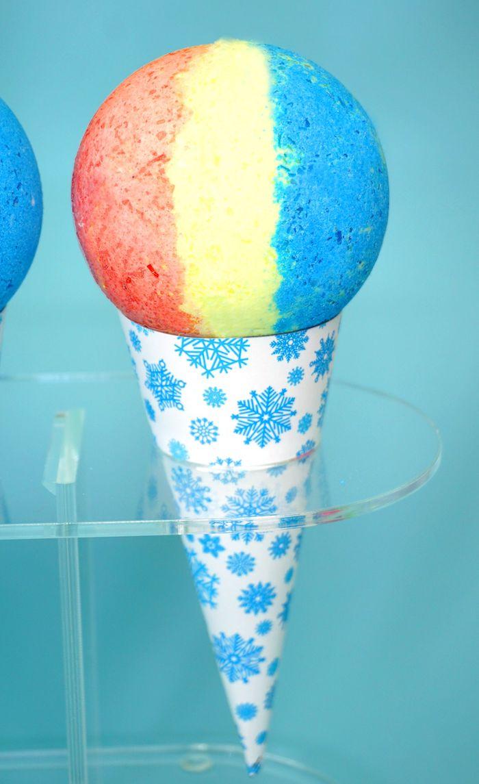 un cone de papier avec des flocons de neige qui tient une boule de bain multicolore