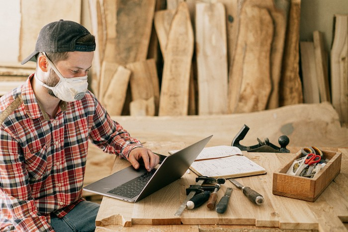 un homme avec masque et casquette devant l ordianteur pose sur une table rustique en bois