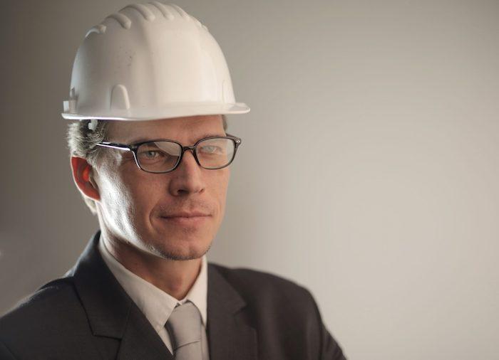 un homme vetu dans un costume noir avec des lunettes et un chapeau dur un maitre d oeuvre