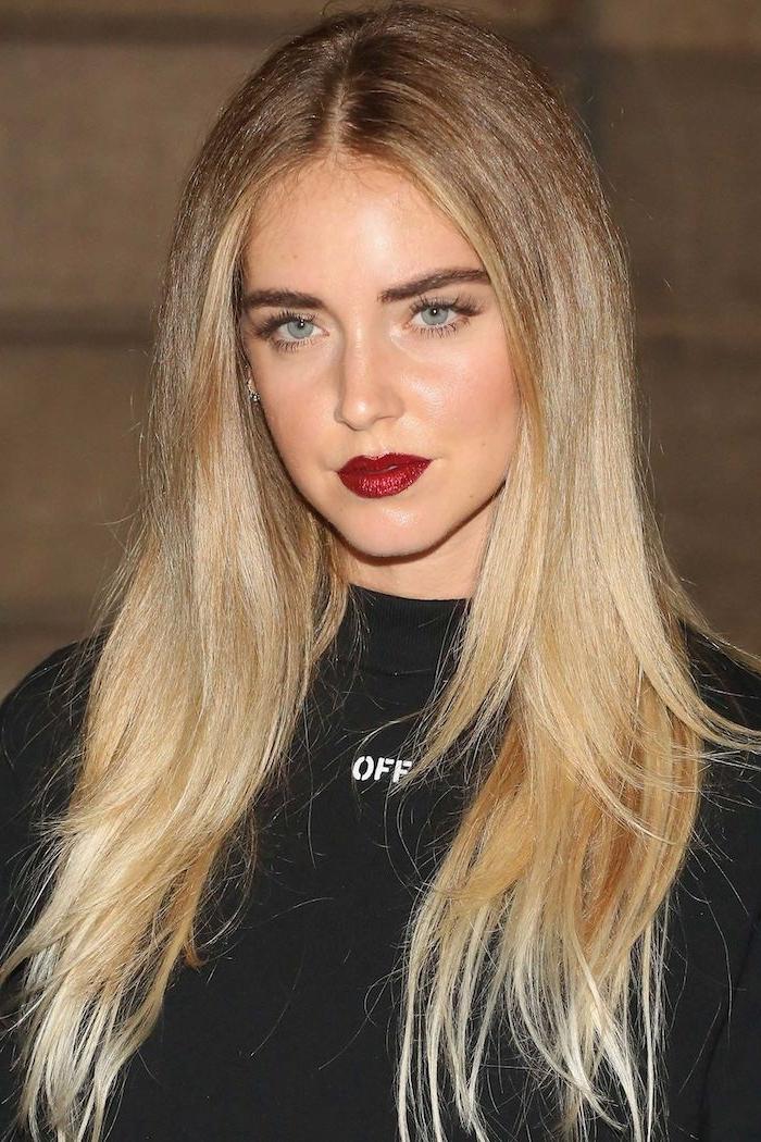 une femme a cehveux blonds longues avec un rouge a levres paillete et des yeux bleus