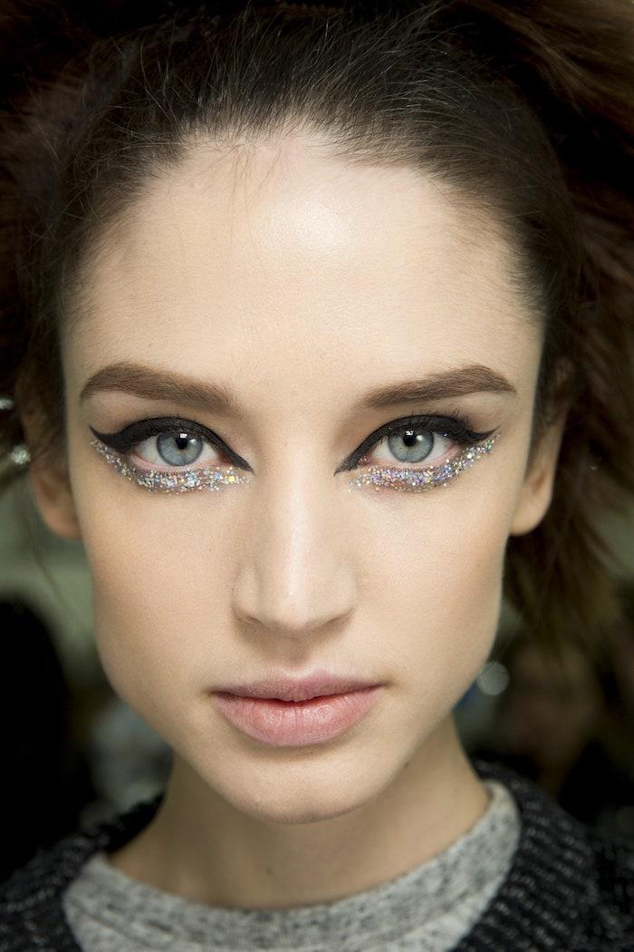 une femme a cehveux bruns et des yeux marrons avec un eye liner paillete sous les yeux maquillage yeux simple