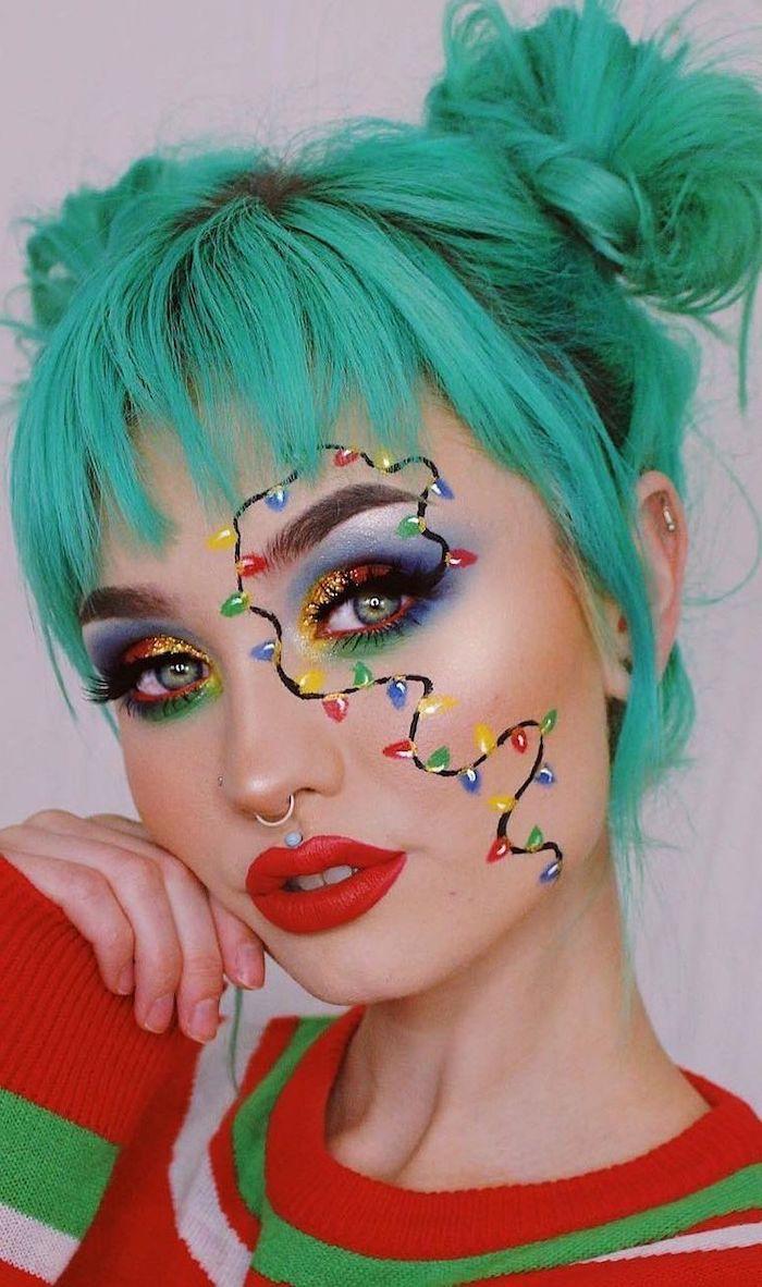 une femme a cheveux vertes vetue en pull en raies avec un maquillage en lampes de noel et un pierce au nez
