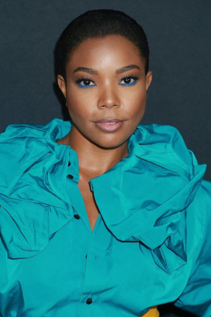 une femme aux cheveux courts avec un eye liner bleu et une blouse turquoise maquillage de soiree