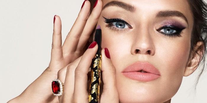 une femme aux yeux bleus qui se fait de maquillage avec un eye liner et des ongles en rouge