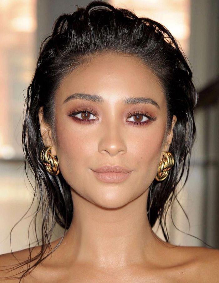 une femme avec des boucles d oreilles en or et un maquillage nude des cheveux en effet mouillé