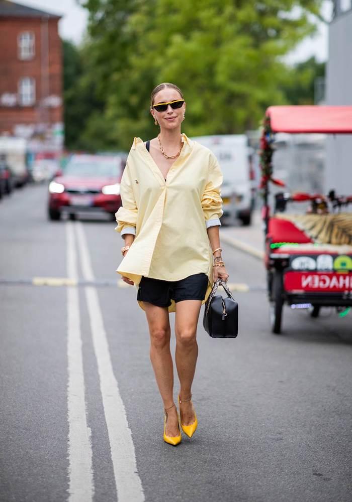 une femme dans la rue avec une chemisier jaune et un pantalon court les couleurs dans la mode