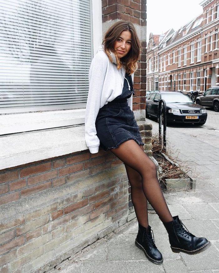 une femme dans la rue vetue en style ds années 90s avec un combinaison en jean collant noir et bottres