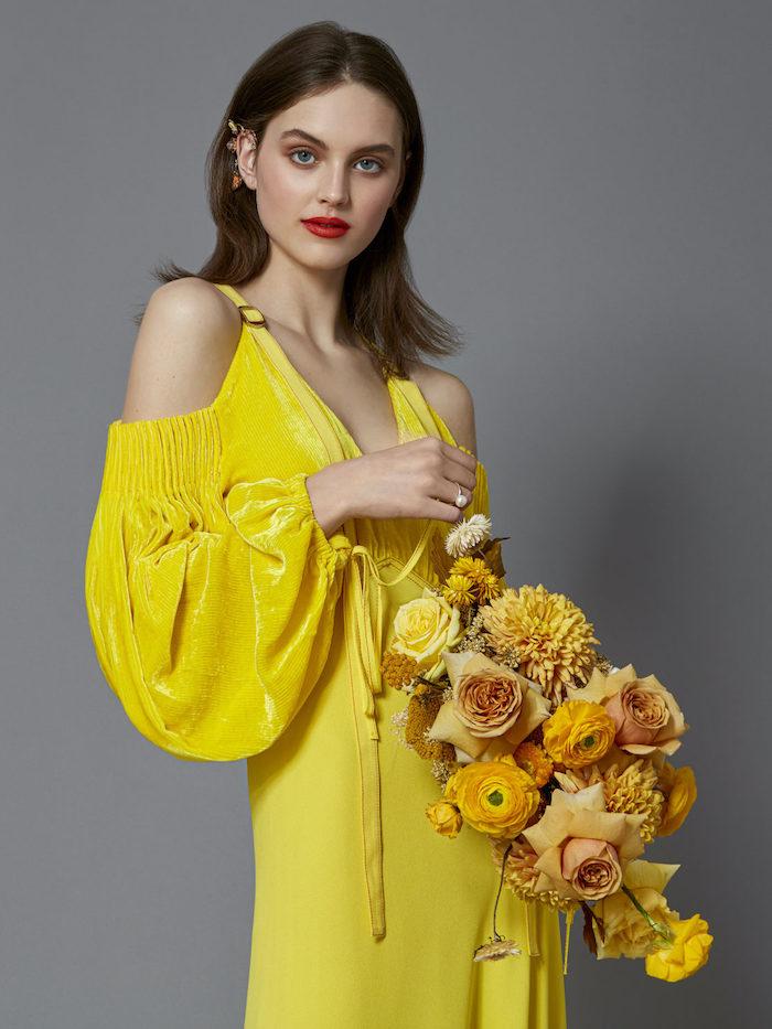 une femme qui tient un bouquet de fleurs oranges vetue en robe jaune au fond gris
