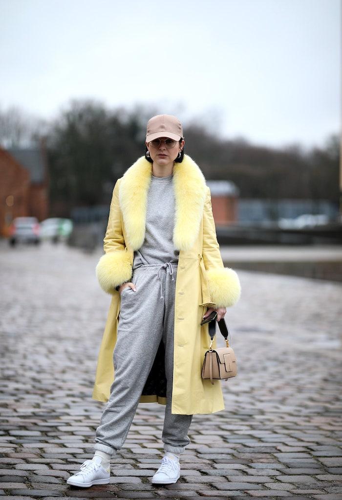 une femme vetue en costume de sport gris et un manteau jaune et casquette brun