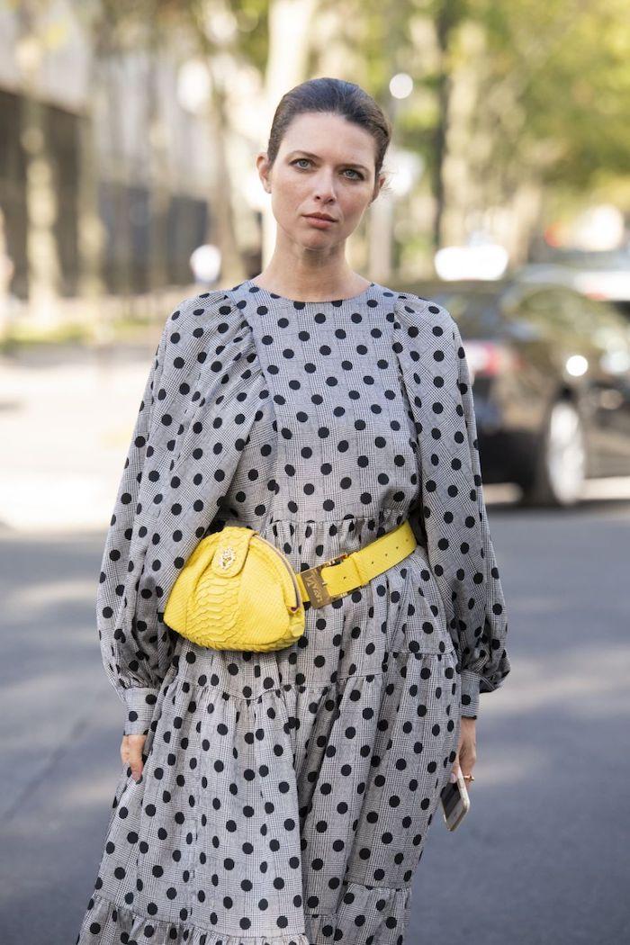 une femme vetue en robe gris a pois et une sacoche jaune pantone 2021