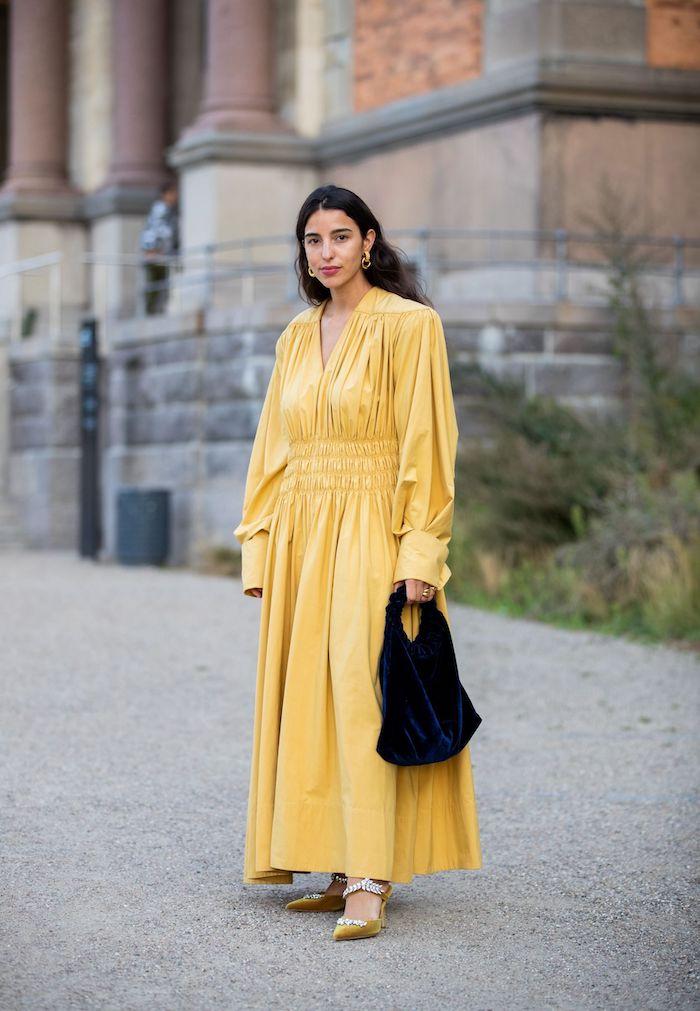 une femme vetue en robe longue jaune avec un sac a main noit devant un edifice culturel