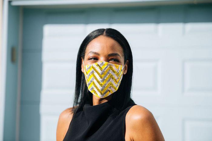 une femme vetue en top noir avec une masque en raies jaunes et blanches paielletes code couleur pantone