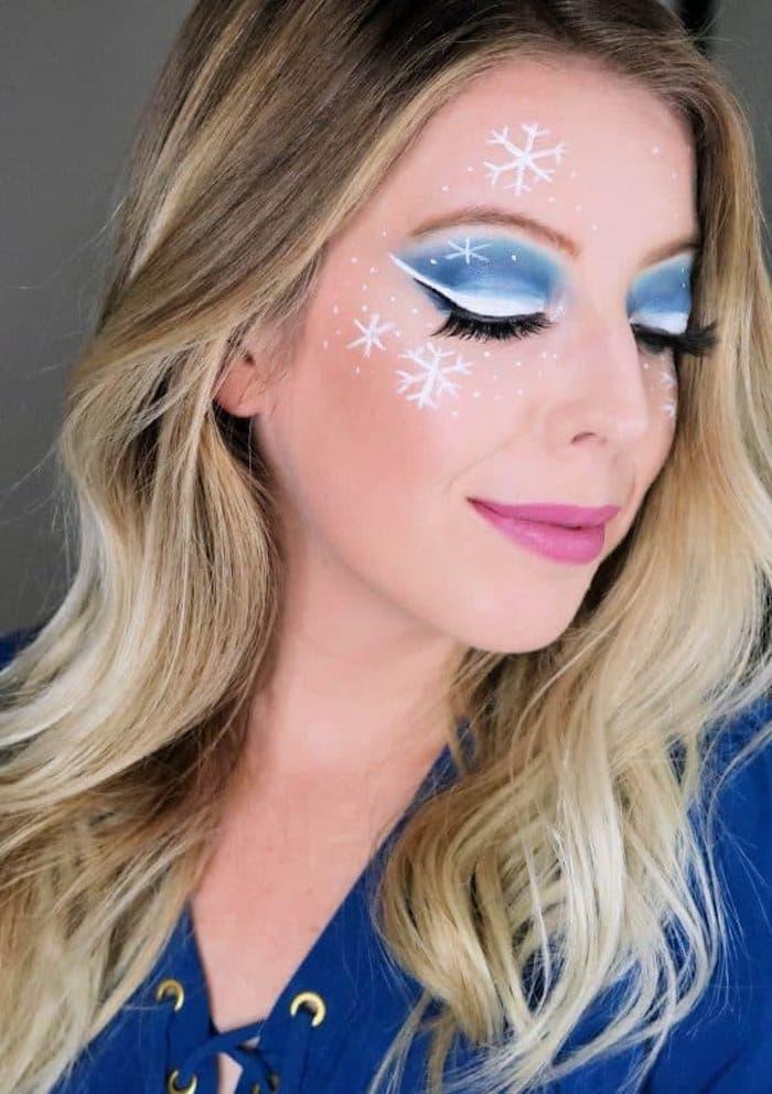 une fille aux longs cheveux blonds avec des flocons de neige dessinees sur le visage idee de maquillade noel