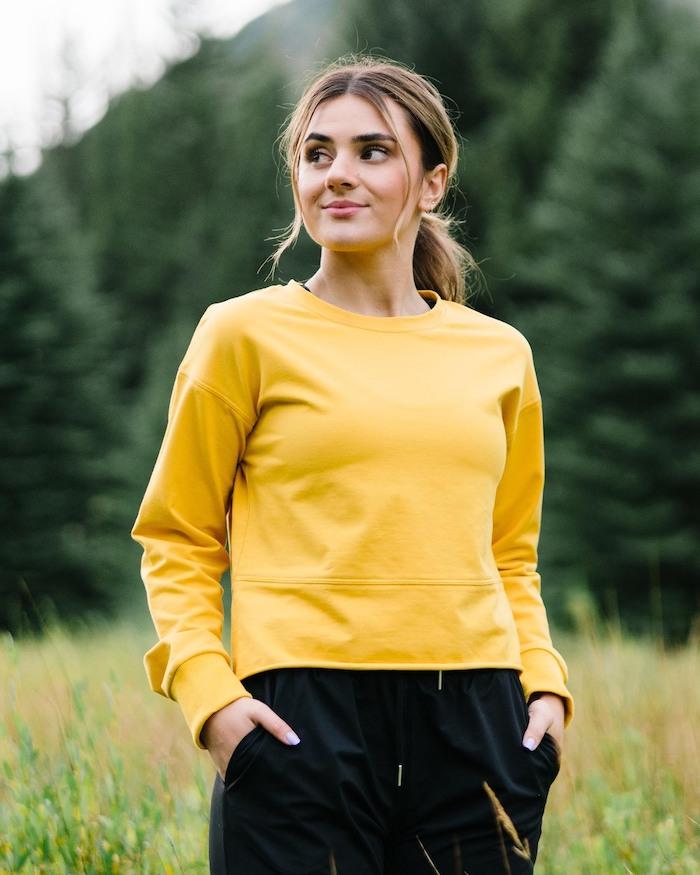une fille dans la nature vetue en pantalon noir et une blouse jaune couleur tendance 2021 couleur pantone 2021