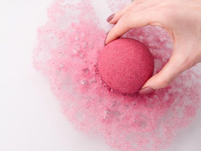 une main femininie qui met une boule de bain dans l eau un couleur de frambois qui se dissous