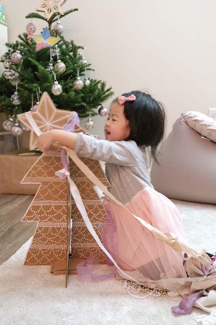 une petite fille vetue en jupe rose met un pointe sur un sapin en carton
