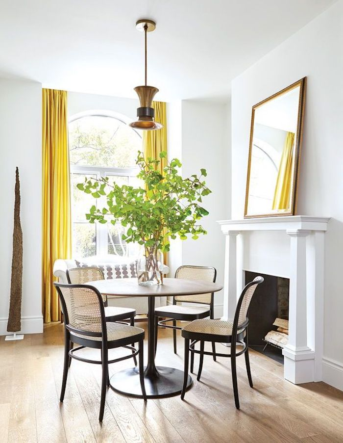 une salle de séjour avec une cheminee table avec quatre chaises et des rideaux jaunes couleur tendance deco 2021