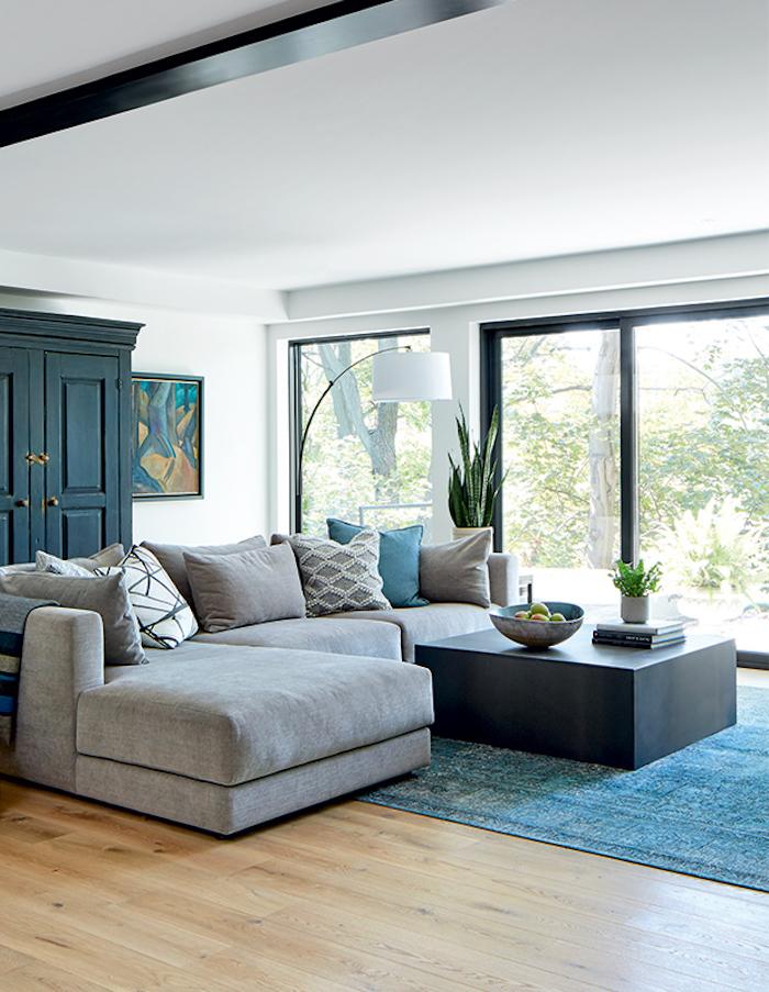 une salle de sejour avec des grandes fenetres un tapis turquois et canape en angle gris couleur tendance deco 2021