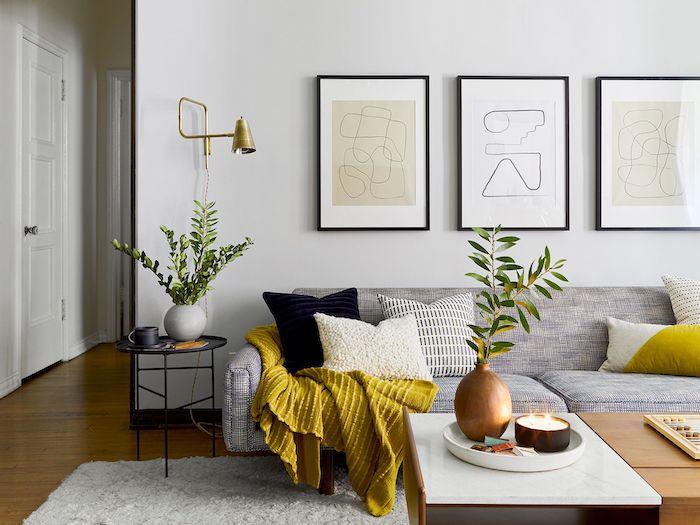 une salle de sejour avec un canape gris et une couette jaune des tableaux aux murs couleur tendance deco 2021