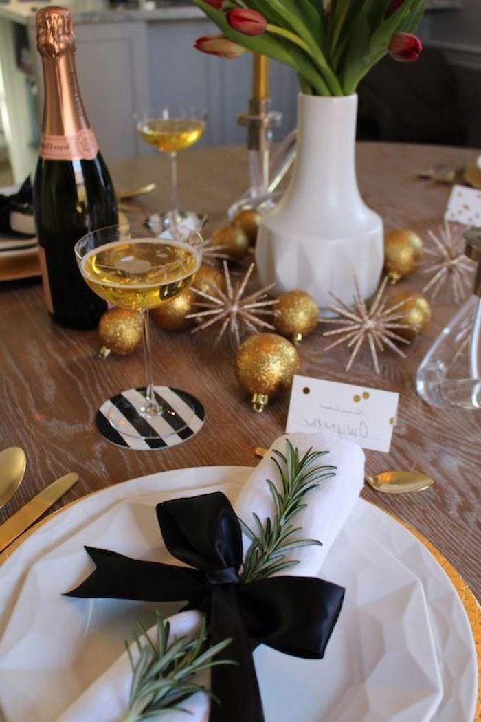 une table decore de reveillon avec es boules dores des branches de romarin et des tulips une bouteille de champagne a cote