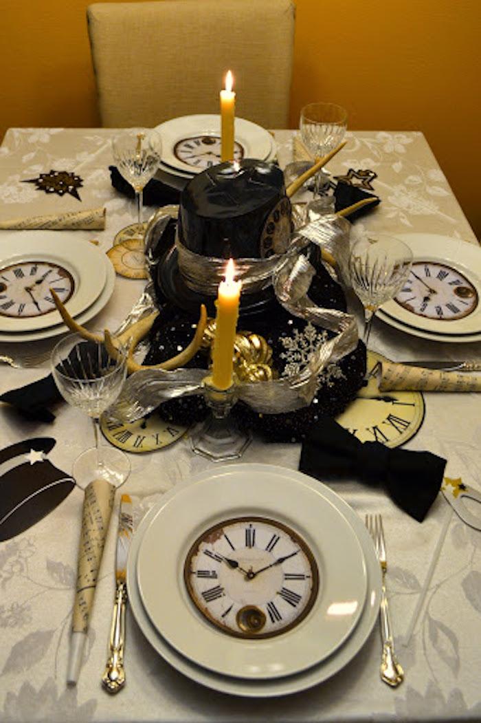 une table decoree pour le jour de l an avec un horologe dessine dans l assiette decorations au milieu de la table et des bougies allumees