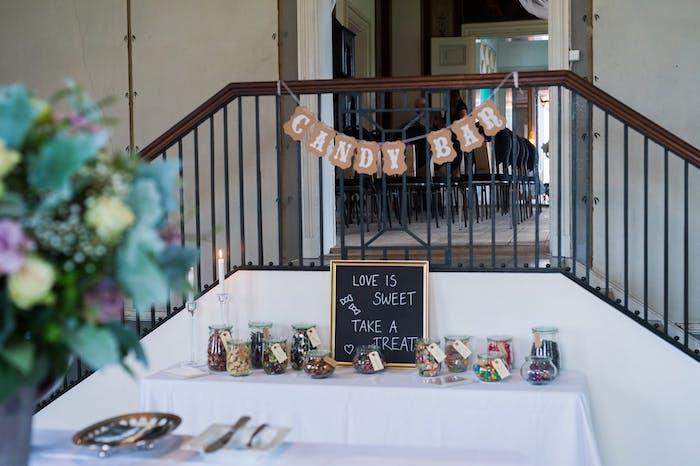 une table organisee comme un candy bar pres d un escalier avec des bonbonnieres