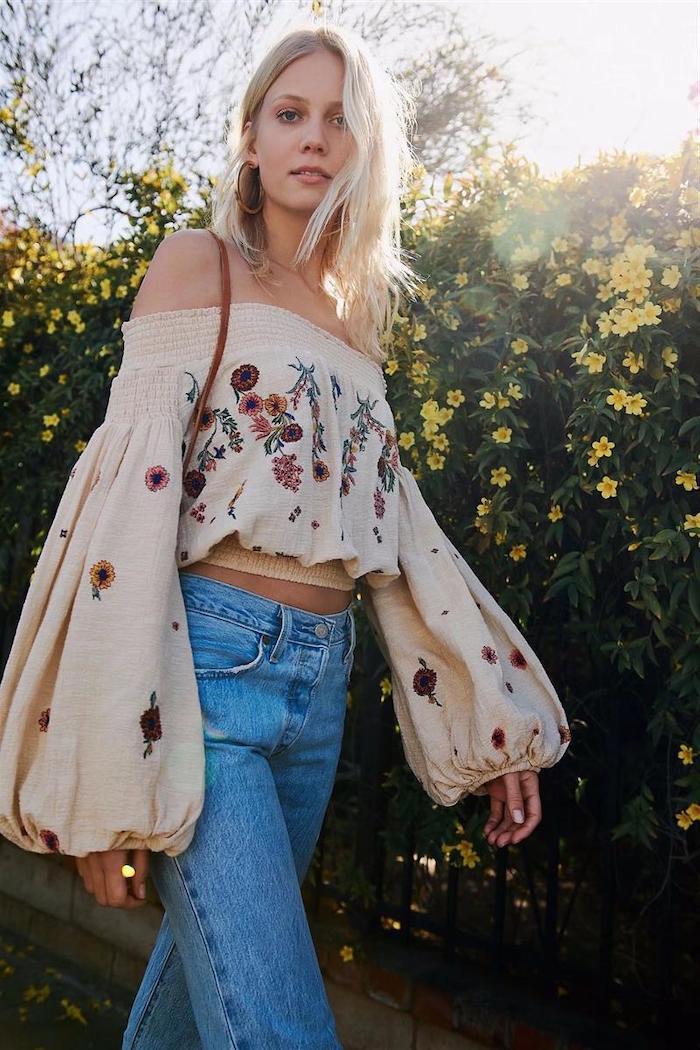 vetement aesthetic d une fille qui porte blouse boho brode et un jean clovhe devant un buisson aux fleurs