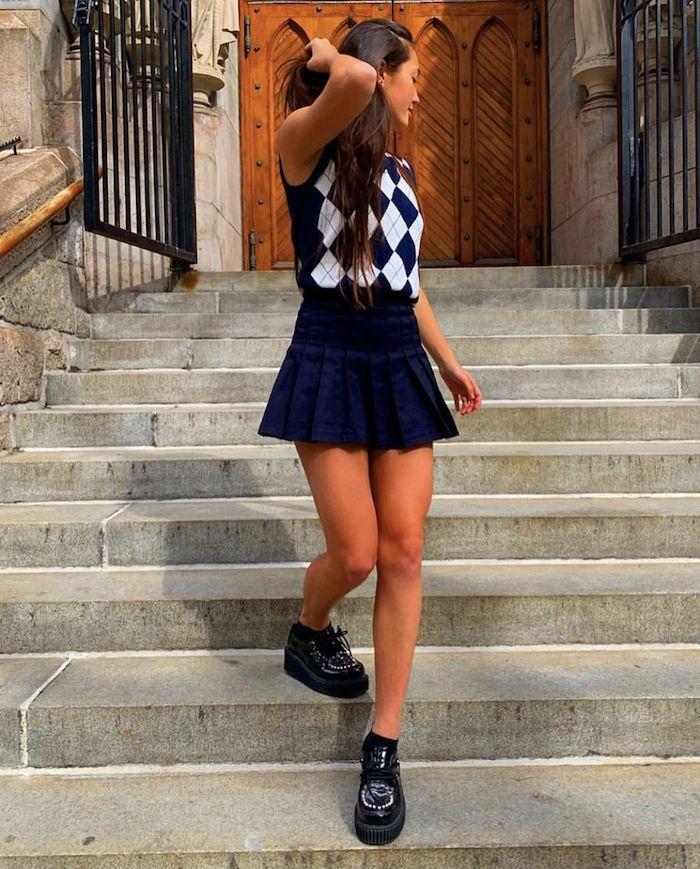 vetement aesthetic une fille sur l escalier vetue en jupe bleu fonce plissée et un pull sans manches