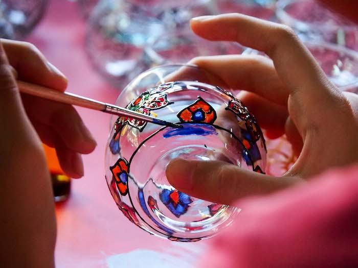 activité créatif adulte pour peinture sur verre deux mains qui dessinent une verre a l aide d un pinceau fin