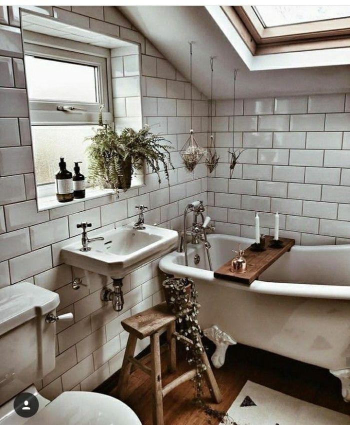 agencement salle de bain sous comble revêtue de carrelage metro blanc baignoire blanche parquet sale de bain plantes suspendues