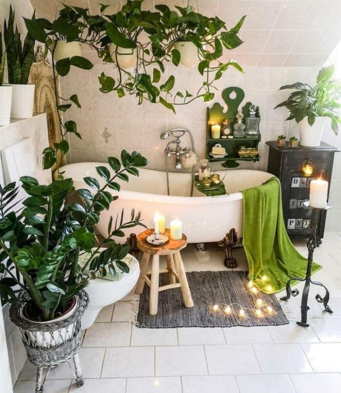 aménagement salle de bain cocooning avec plusieurs plantes vertes salle de bain carrelage sol et murs bougies guirlande lumineuse autour d une baignoire blanche