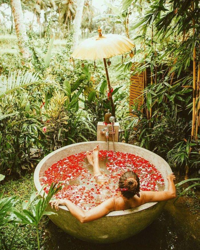 ambiance salle de bain zen à l extérieur avec des pétales de fleur dans cadre naturel avec des bambous et autres plantes vertes autour