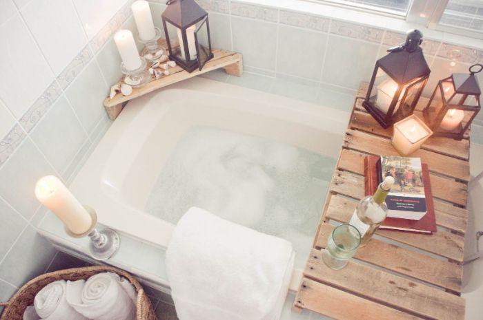 amenagement salle de bain cosy avec pont de baignoire bois paniers avec des serviettes rangées à l intérieur bougeoirs lanternes