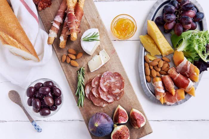 amuse bouche apéritif facile un petit plateau avec des charcuteries et formages a cote d une assiette metallique avec des fruits