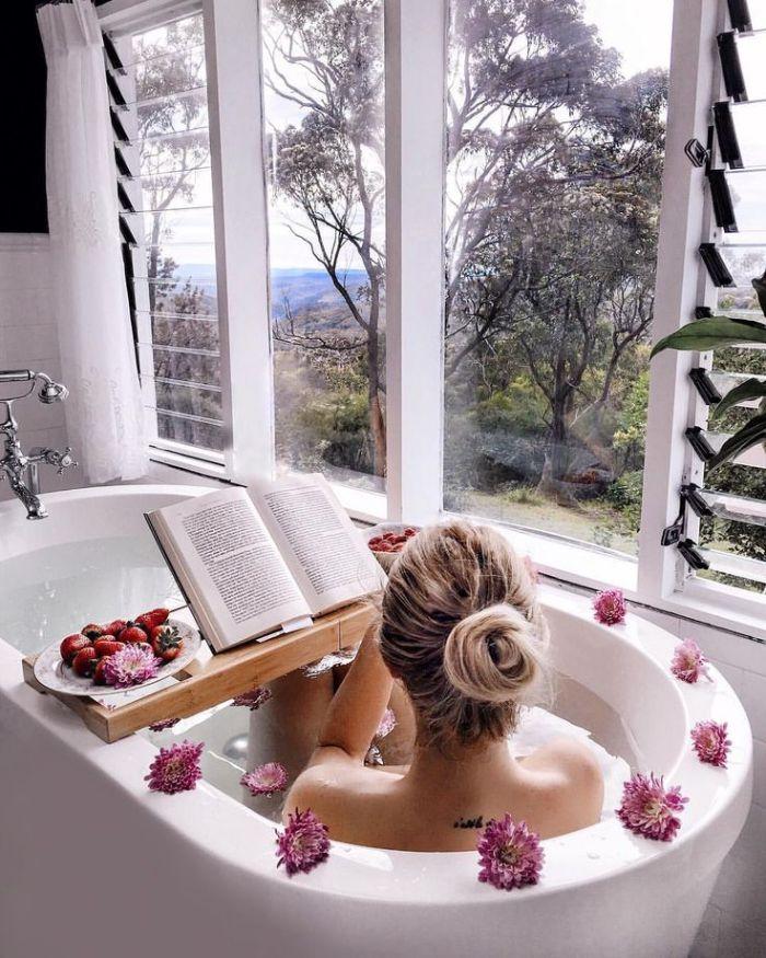baignoire blanche avec belle vue sur l extérieur et decoration de fleurs pont de baignoire avec de fruits servis lecture livre