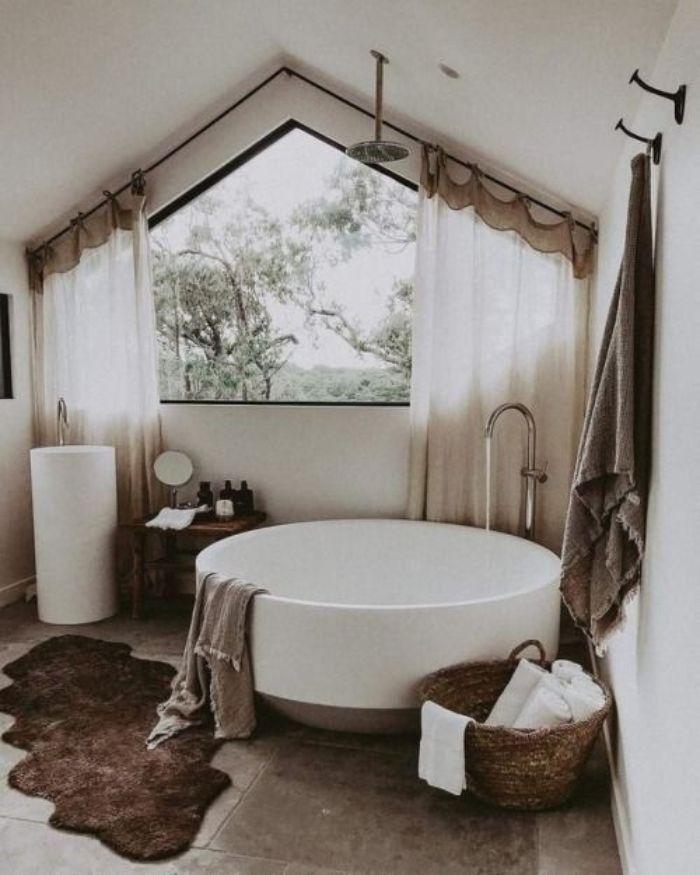 baignoire blanche dans salle de bain blanche et grise avec tapis marron foncé panier rempli de serviettes blanches sdb sous comble