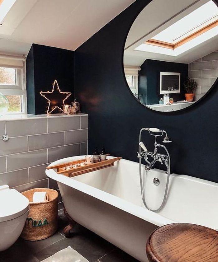 baignoire blanche dans salle de bain noire miroir rond panier tressé table plteau service bois ambiance cosy