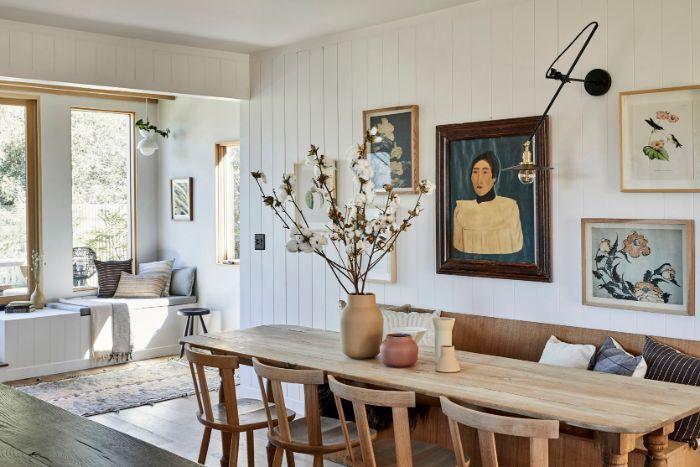 banc chaises et table de bois parquet bois clair murs revetus de lambris blanc tableaux d art japonais coin lecture coté fenetre