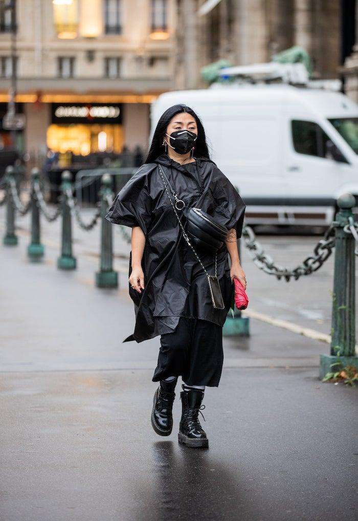 bottine doc martens avec une veste noir avantgardiste et moderne une femme avec une masque sur le visage